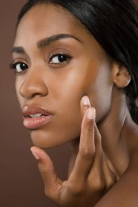 Young Woman Applying Foundation --- Image by © Image Source/Corbis