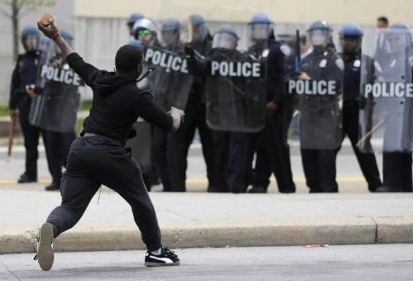 A man throws a brick at police Monday, April 27, 2015, following the funeral of Freddie Gray in Baltimore. Gray died from spinal injuries about a week after he was arrested and transported in a Baltimore Police Department van. (AP Photo/Patrick Semansky)
